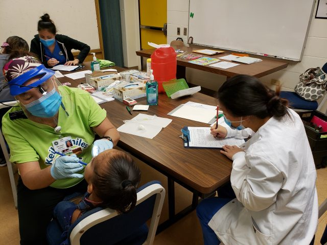 dental hygienist students work on children's teeth