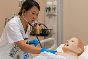 graduate entry program in nursing student with manikin in simulation lab