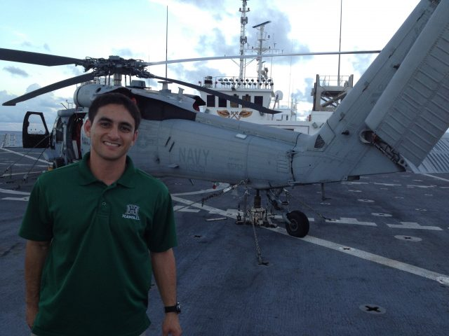 student poses with Navy Helicopter