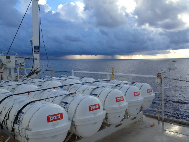 photo of life raft pods Lined up along the deck, with an endless Pacific Ocean as a backdrop.