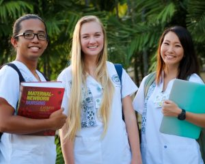 three nursing students pose for photo with study materials