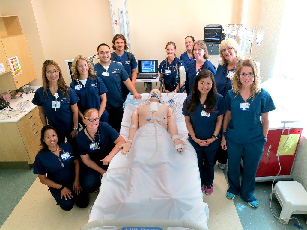 students pose for group photo with dummy patient