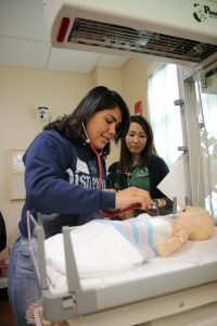 Students with infant manikin in sim lab