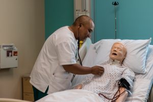 graduate entry program in nursing student with manikin in simulation lab