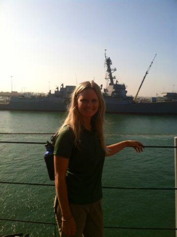 student smiles next to USS Pearl Harbor